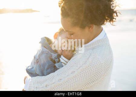Young woman embracing daughter on beach - Stock Photo