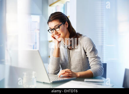 Female office worker sitting at desk using laptop - Stock Photo