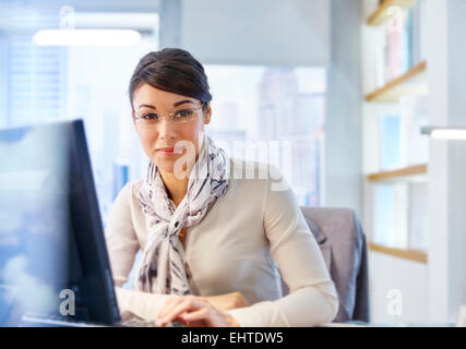 Female office worker sitting at desk using computer,portrait - Stock Photo