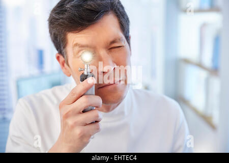 Man looking through illuminated speculum in laboratory - Stock Photo