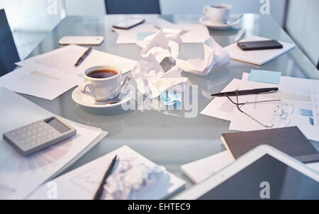 Messy table in conference room of modern office - Stock Photo