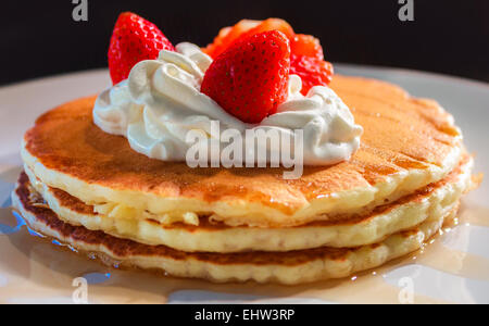 Three American pancakes in a stack with whipped cream and strawberries on top. - Stock Photo