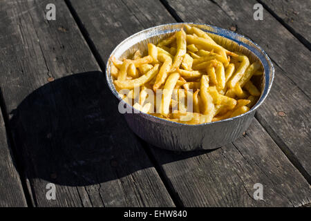 French fries in aluminum foil tray. Served over old wooden picnic table - Stock Photo