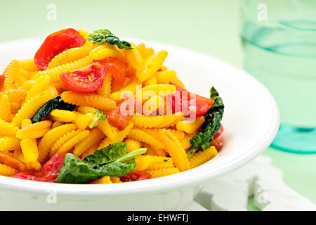 Sardinian dumplings, a traditional pasta from semolina or durum wheat flour served with fresh tomato and spinach - Stock Photo