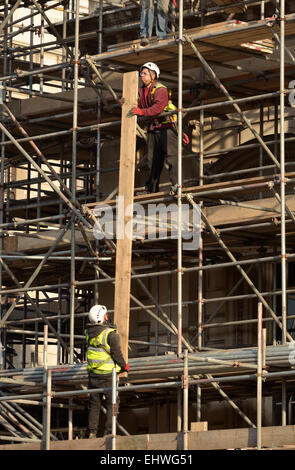 London, England, UK. Construction workers passing long planks up scaffolding - Stock Photo