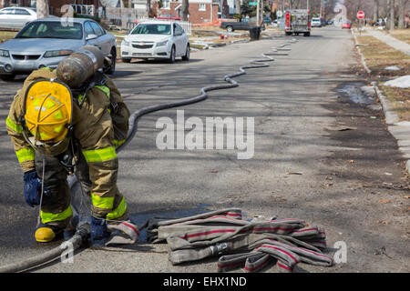 Detroit, Michigan - A firefighters connects hoses while fighting a fire which destroyed a vacant home in Detroit. - Stock Photo