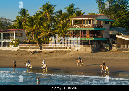 Horse riding on Poneloya Beach, a popular little Pacific Coast resort  west of the northern city of Leon; Leon, - Stock Photo
