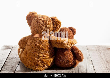 Two teddy bears, arm on shoulder, back view on wood - Stock Photo
