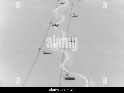 Ski track in deep snow with shadows from a chair lift, Venet, Zams, Tyrol, Austria - Stock Photo