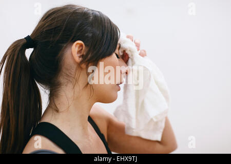 Young woman wiping off sweat from her forehead - Stock Photo