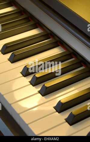 Piano keyboard close-up in warm lamp light - Stock Photo
