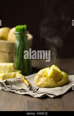 Steaming baked jacket potato with chives and mature cheddar cheese - Stock Photo