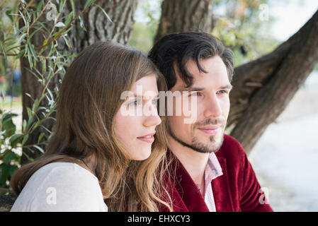 Close up portrait young couple sitting lake