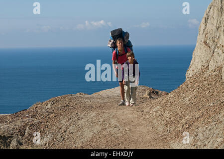 The woman and her daughter moves with backpacks along the rock. Tourists are situated against the blue sea and sky - Stock Photo