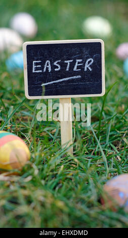 Easter written on a chalkboard standing in grass between easter eggs - Stock Photo
