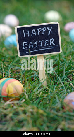 Happy easter written on a chalkboard standing in grass between easter eggs - Stock Photo