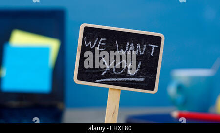 We want you written on a chalkboard, in the background a office - Stock Photo