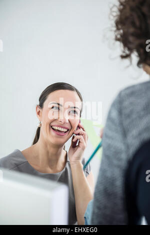 Businesswoman talking on mobile phone in an office, Munich, Bavaria, Germany - Stock Photo
