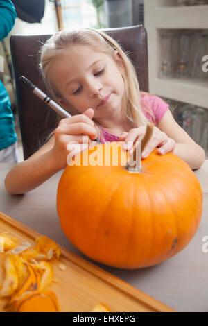 Girl carving pumpkin for Halloween, Bavaria, Germany - Stock Photo