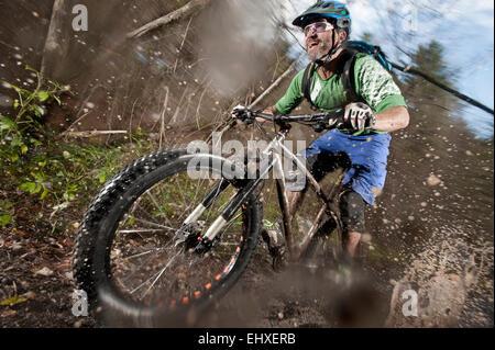 Mountain biker riding on a dirt road, Bavaria, Germany - Stock Photo
