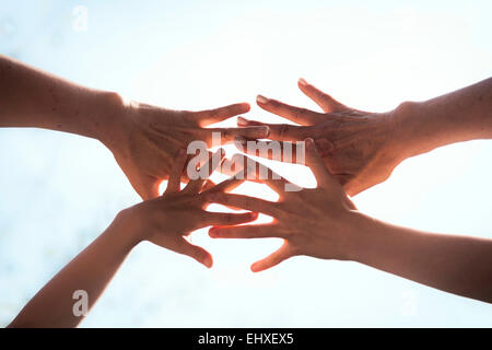 Close up of a family hands together against sunlight, Bavaria, Germany - Stock Photo