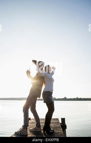 Young happy couple dancing jetty sunset - Stock Photo
