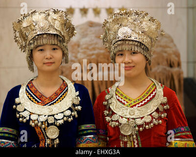 Portrait of two young women wearing traditional Miao ethnic minority clothing outfits in Guilin, China - Stock Photo