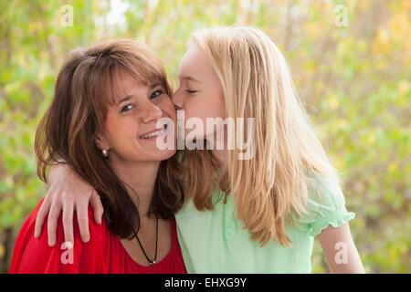 Girl kissing her mother, Bavaria, Germany - Stock Photo