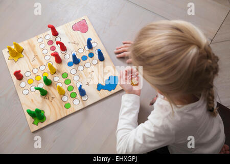 Girl playing board game, Bavaria, Germany - Stock Photo