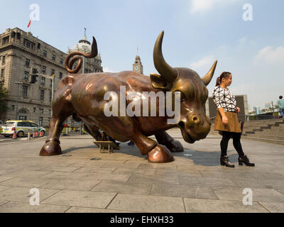 Women poses with the Bund Financial Bull bronze sculpture in Shanghai, China, Asia - Stock Photo