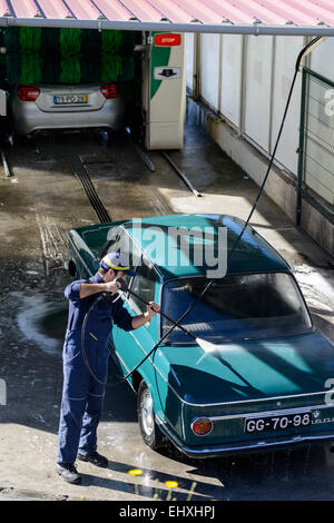 Young man washing car with high pressure water hose at a professional car wash - Stock Photo