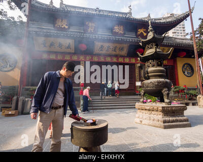 Man lighting joss stick incense at the courtyard of the Jade Buddha temple in Shanghai, China - Stock Photo