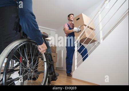 Removal man carrying cardboard box upstairs, Bavaria, Germany - Stock Photo