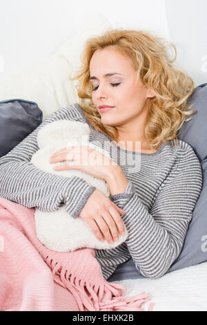 Woman lying on couch with hot water bottle - Stock Photo