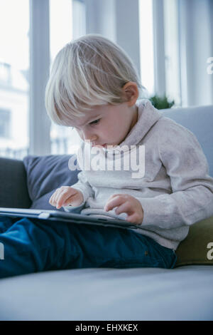 Little boy sitting on the couch playing with digital tablet - Stock Photo