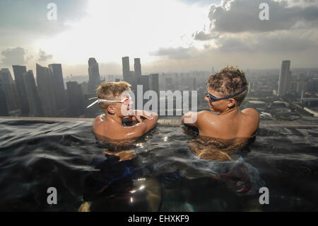 Teenage boys in an infinity pool, Marina Bay Sands, Singapore City, Singapore - Stock Photo