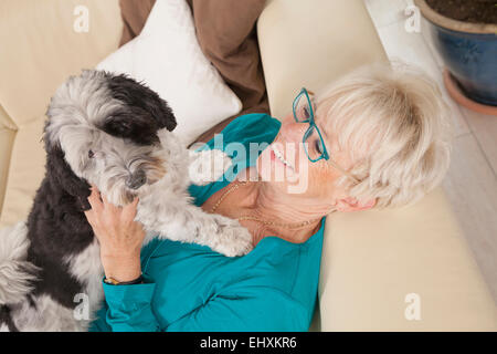 Senior woman playing with her dog, Bavaria, Germany - Stock Photo