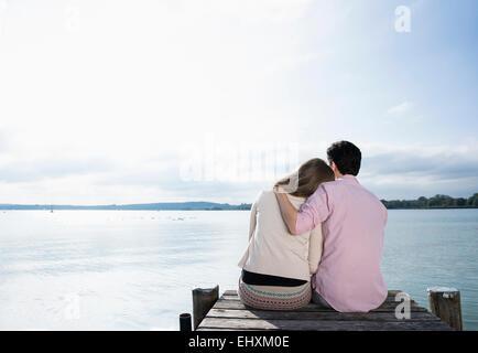 Romantic couple hugging lake jetty tranquil - Stock Photo