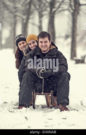 Group picture of three friends sitting on sledge in winter - Stock Photo