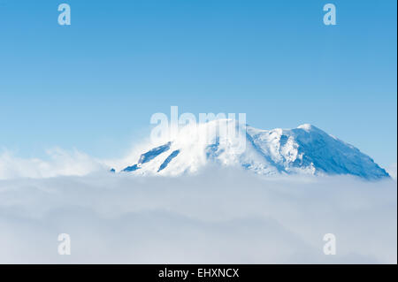 Aerial view of Mt. Rainier peeking over a cloud layer with clear blue sky above and wind whipping snow off the peak - Stock Photo