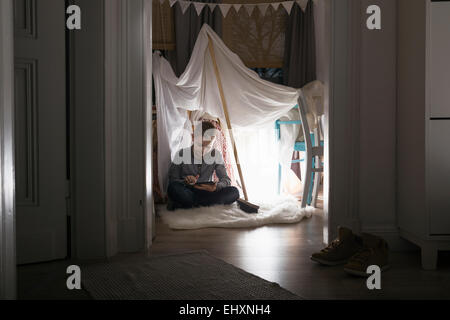 Boy sitting in self-made tent at home in the evening using digital tablet - Stock Photo