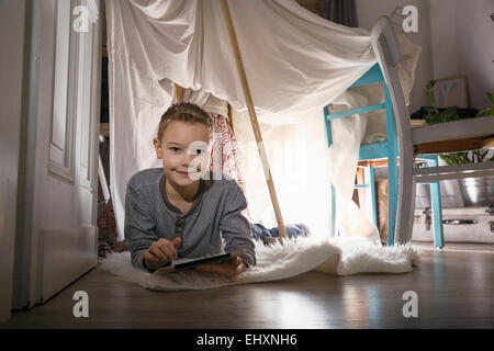 Boy digital tablet lying in self-made tent at home in the evening - Stock Photo