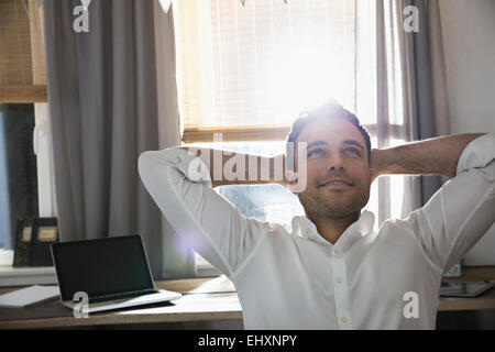 Portrait of happy man with hands behind his head at his home office - Stock Photo