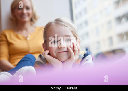 Smiling girl with mother in background - Stock Photo
