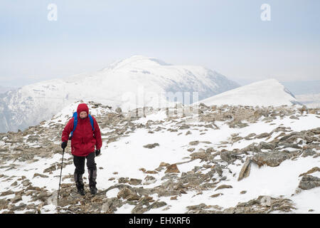 Male hiker in red jacket hiking in snow on rocky Y Garn mountain top in Snowdonia National Park (Eryri). Ogwen, - Stock Photo