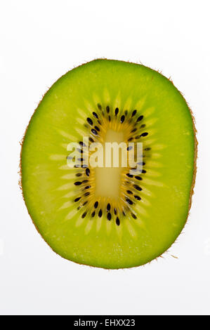 Cross-section of sliced Kiwi fruit (Actinidia chinensis) showing inner pulp with fruit flesh and seeds, native to - Stock Photo
