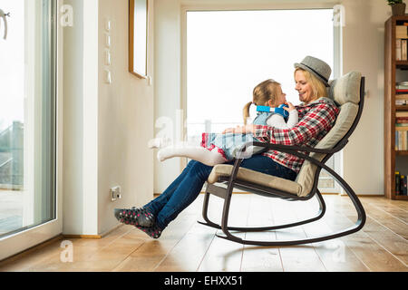 Merveilleux ... Mother And Daughter On Rocking Chair With Headphones   Stock Photo