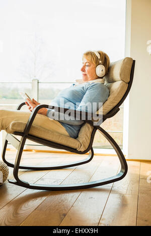 Senior woman at home with headphones and digital tablet - Stock Photo