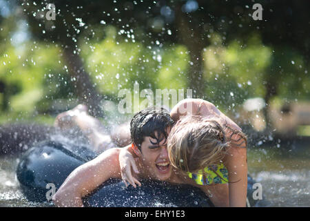 Young couple on holiday having fun with inner tube in a pool - Stock Photo