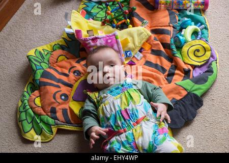 8 month old baby girl, lying on floor - Stock Photo